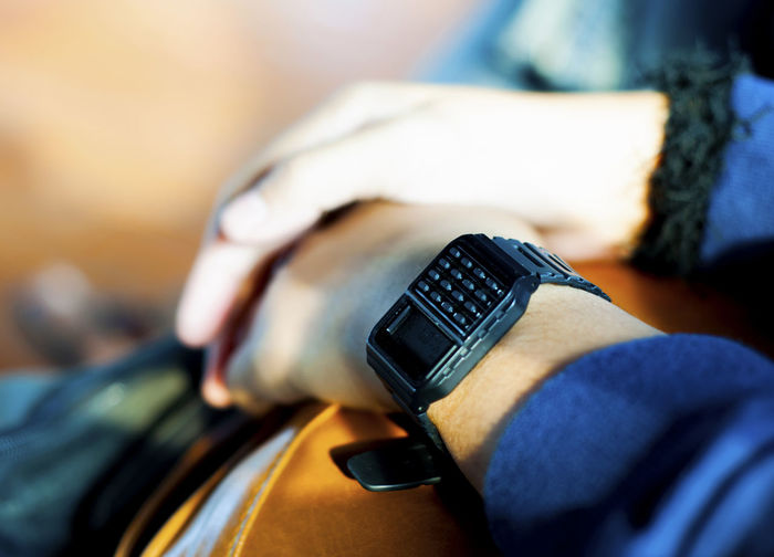 Midsection of person wearing keypad wristwatch