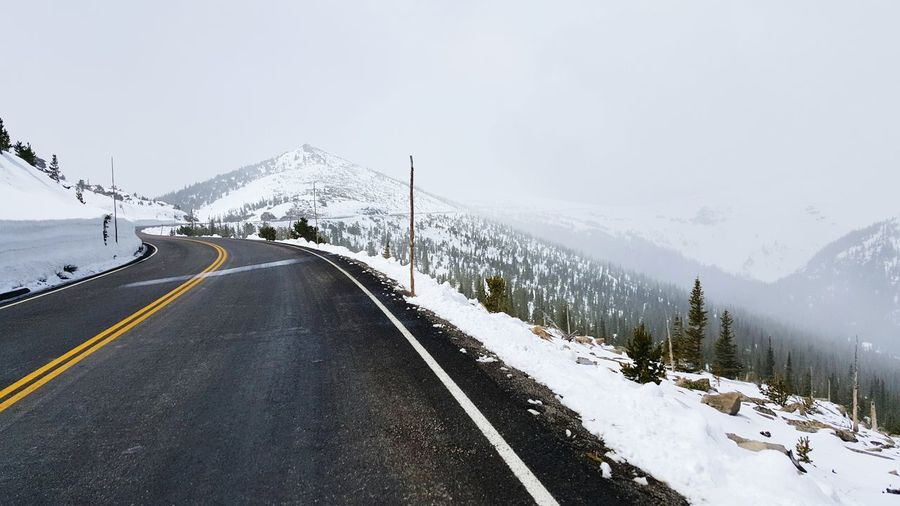 Empty road passing on snowcapped mountain