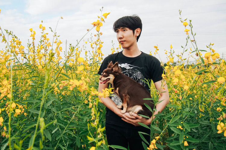 Day Dog Flower Grass Holding One Person Only Men Outdoors People Plant Yellow Flower HolidayMarketing Uniqueness Let's Go. Together.