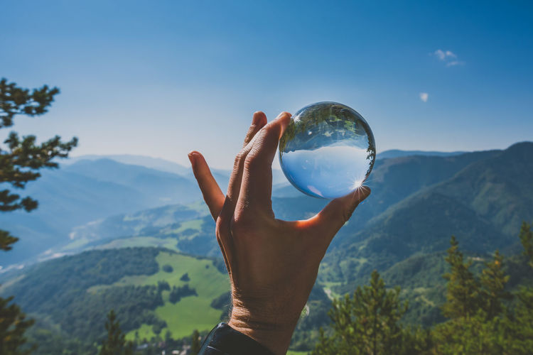 Cropped hand holding crystal ball against mountains