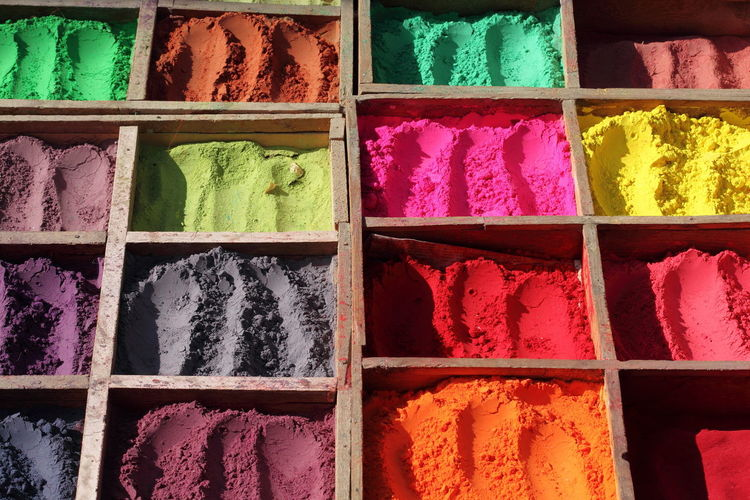 Full frame shot of colorful powder paints in wooden containers at market stall