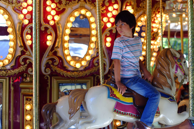Boy looking away while sitting on carousel horse