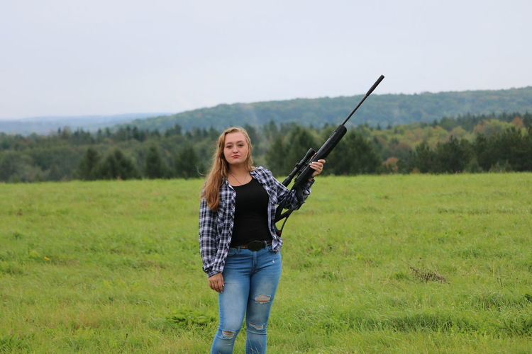 Senior photo shoot Adult Beautiful Woman Casual Clothing Day Field Front View Grass Gun Hairstyle Holding Hunter Land Leisure Activity Nature Non-urban Scene One Person Outdoors Plant Portrait Smiling Standing Weapon