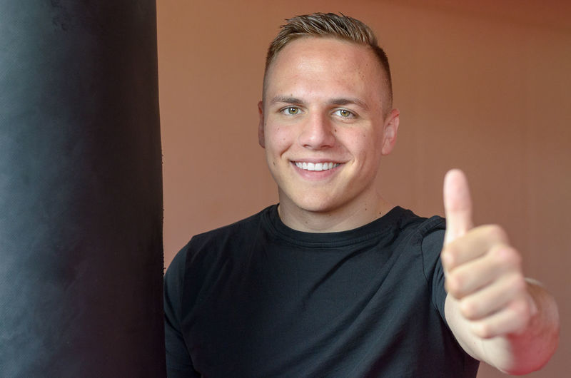 Portrait of man gesturing thumbs up sign by punching bag against wall