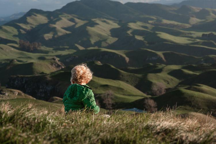 Rear view of boy on arid landscape