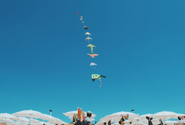 Low angle view of people flying kites against clear blue sky