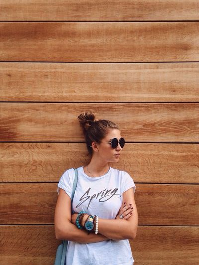 Woman wearing sunglasses standing against wooden wall
