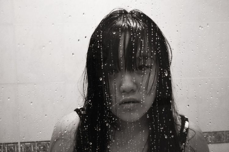 Close-up of woman on wet glass