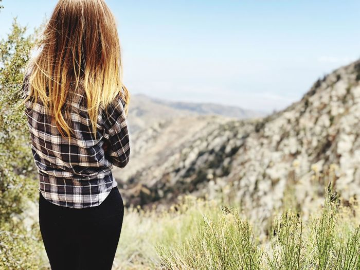 Rear view of woman with blond hair standing on mountain