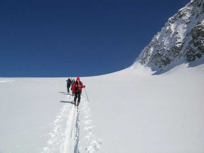 Rear view of people walking on snowcapped mountain against clear sky
