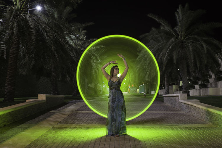 Woman standing by palm tree at night