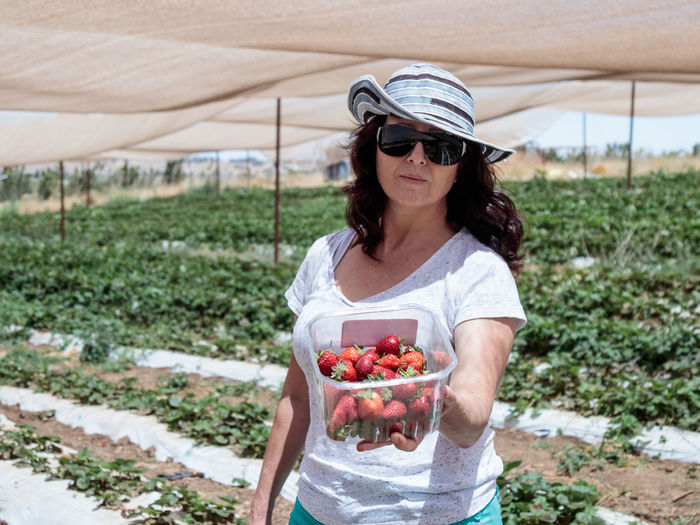 Portrait of woman holding strawberries in container while standing at farm during sunny day