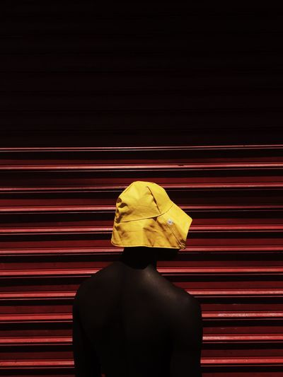 Close-up of mannequin wearing yellow bucket hat by closed shutter