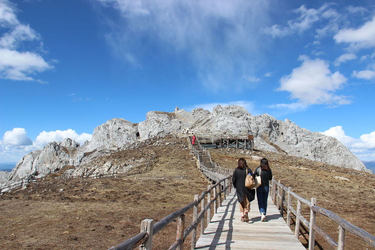 Rear view of people walking on mountain against sky