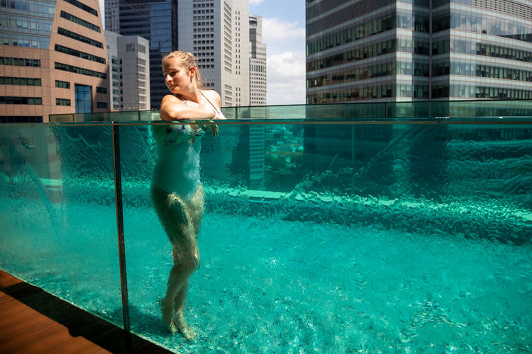 Beautiful woman resting in the pool against the background of the cityscape