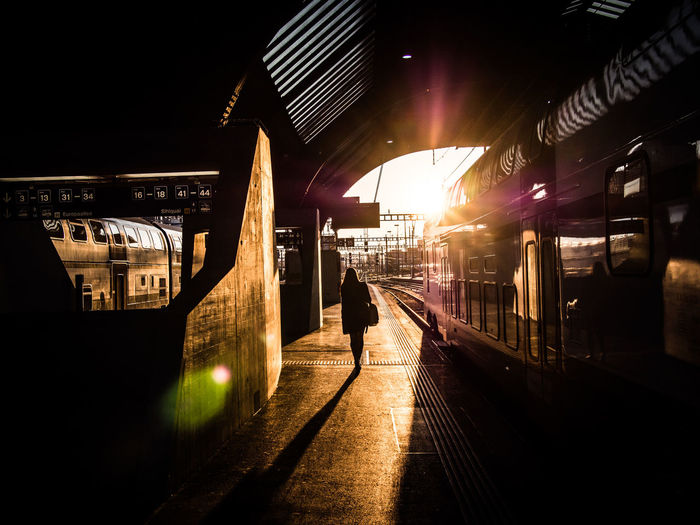 Man and woman standing on railroad station platform at night