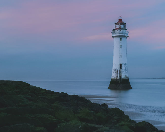 Lighthouse by sea against sky at sunset