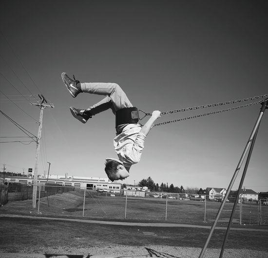 Full length of man swinging on swing against sky