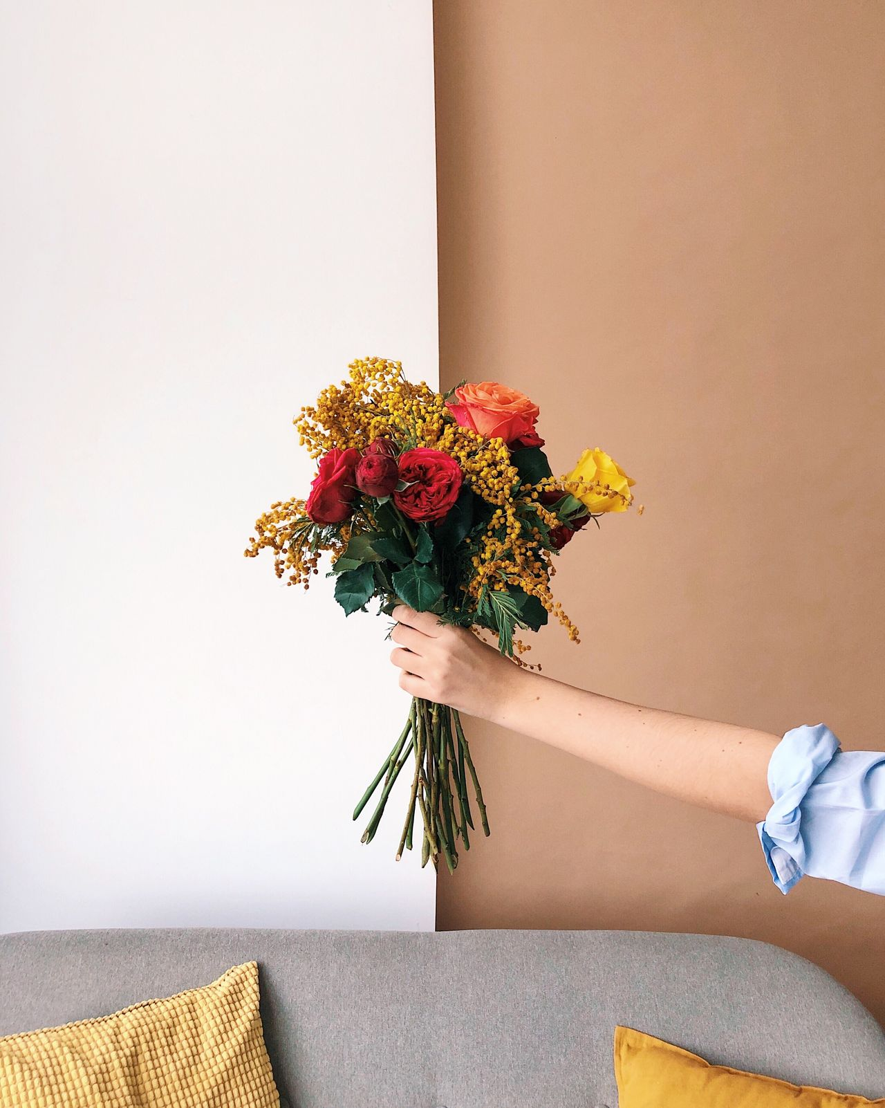 Cropped hand of hand holding bouquet against wall