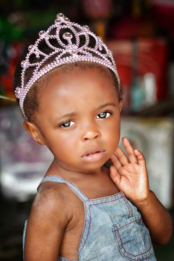 Close-up portrait of cute baby girl wearing crown at home