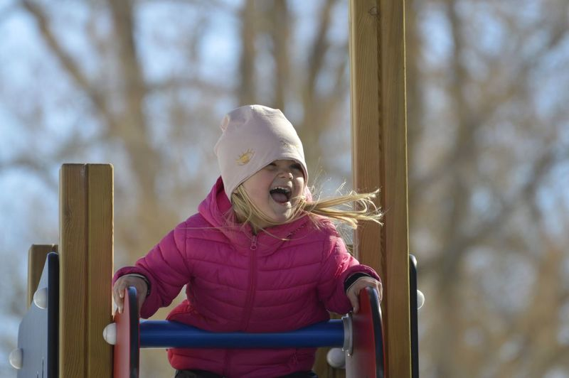 Low angle view of cheerful girl on play equipment