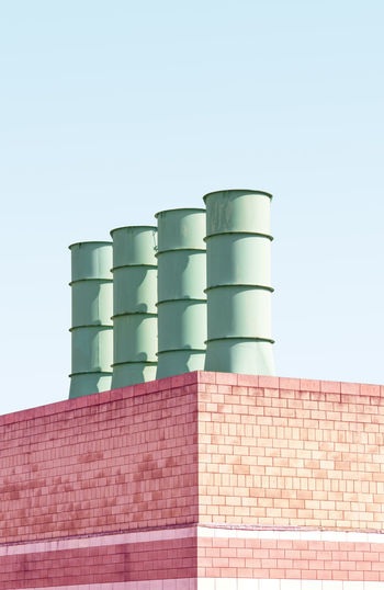 Low angle view of smoke stacks on building against clear sky