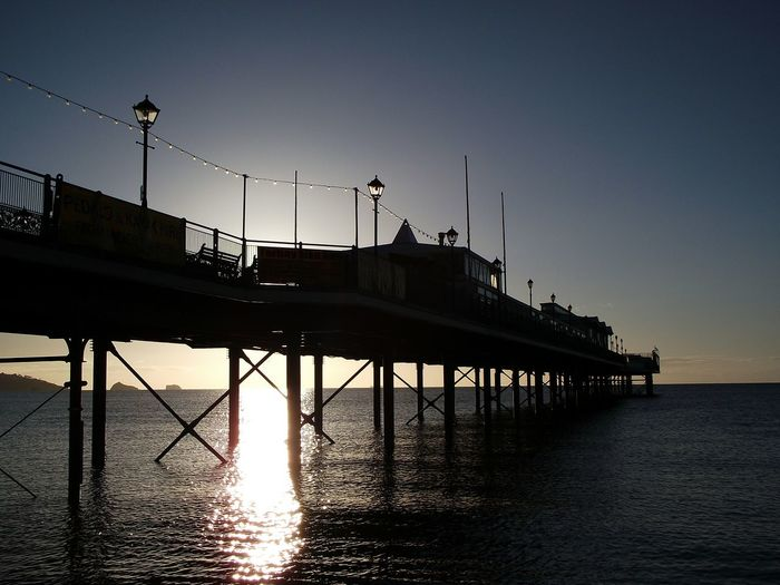 Silhouette pier over sea during sunset