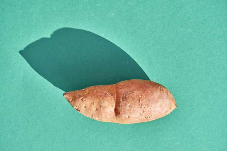 Directly above shot of sweet potato against turquoise background