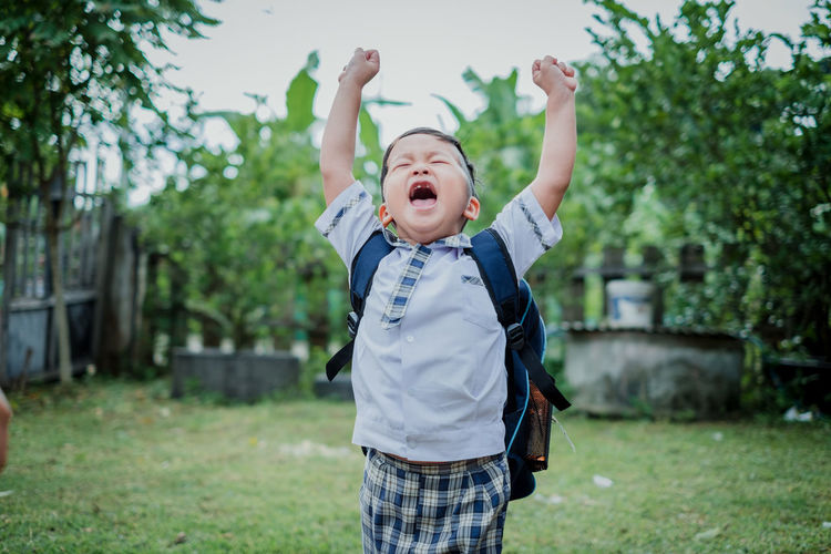Happy children go back to school.Asian smiling boy with two fingers up going to school for the first time. ASIA Asian  Back Background Backpack Bag Beginning Book Boy Business Caucasian Cheerful Child Childhood Classroom Concept Copy Space Cute Education Elementary Face Fingers First Gesture Graduation Hand Happy Kid Knowledge Learn Little Little Boy Male One Person People person Portrait Preschool Pupil School Showing Sign Smart Smiling Student Success Teenager Two Fingers Uniform Young