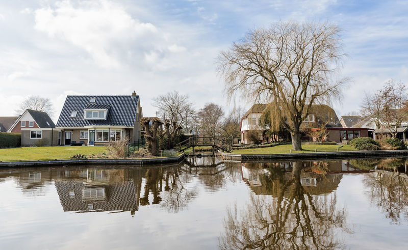 Modern detached houses on the waterfront of a town canal in Hindeloopen, Netherlands. Modern Modern Architecture Architecture House Home Water Waterfront Canal Canals And Waterways Front Or Back Yard Building Exterior Built Structure Hindeloopen Friesland Netherlands Detached House New Wealth Reflection Garden Townhouse Tree Winter Europe Town Canal