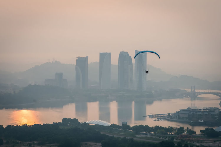 Parachute flying above river in foggy weather during sunrise