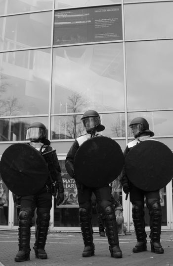 Riot police in Amsterdam during demonstrations for and against refugees in Europe Amsterdam Police Politie Riot Riot Gear Riot Police Opéra Refugeeswelcome Refugees Pegida Being Cultured Blackandwhite Officers Trio