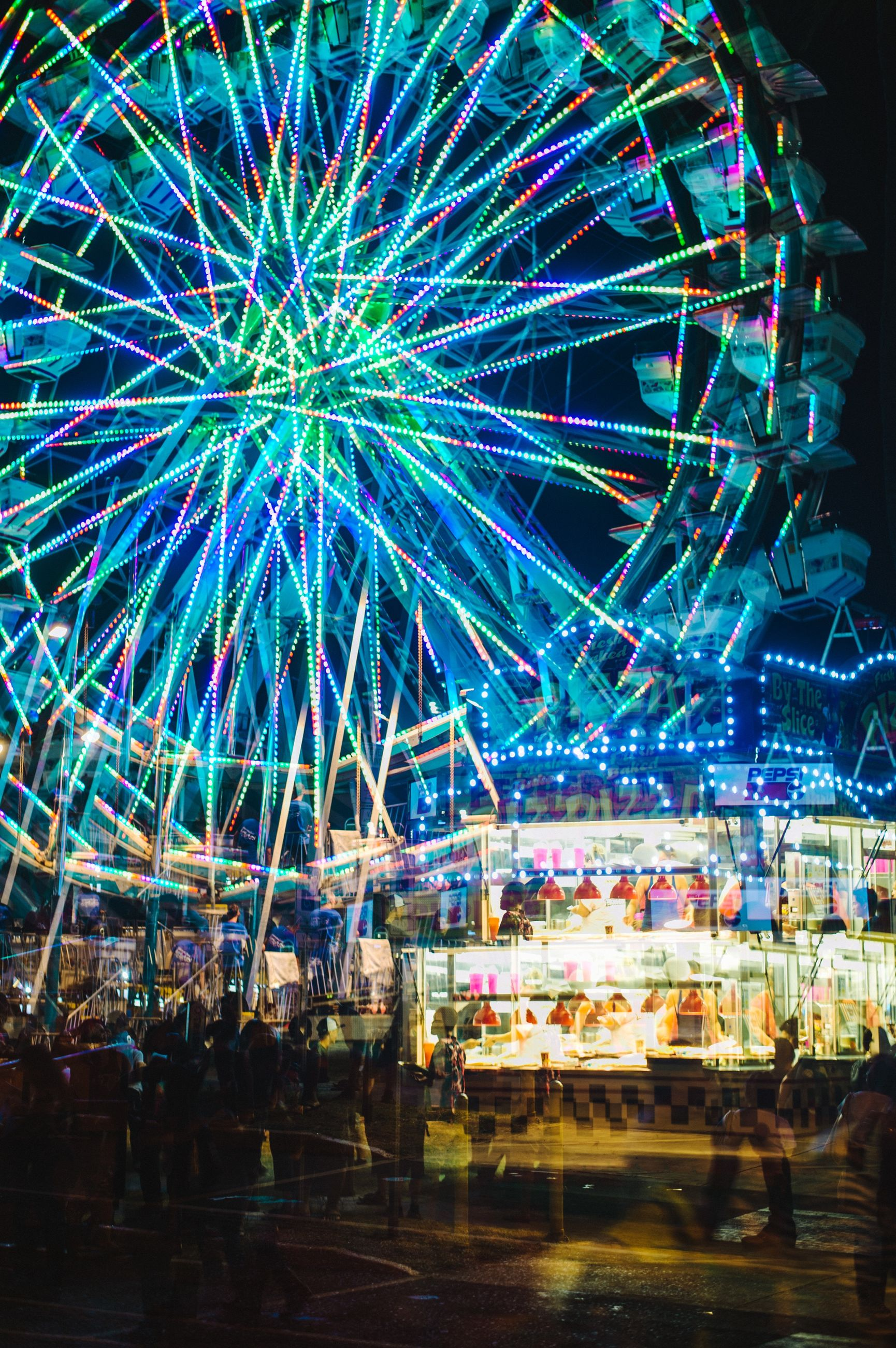 illuminated, night, arts culture and entertainment, amusement park, amusement park ride, long exposure, motion, built structure, ferris wheel, architecture, blurred motion, firework display, celebration, multi colored, building exterior, glowing, lighting equipment, low angle view, city, incidental people