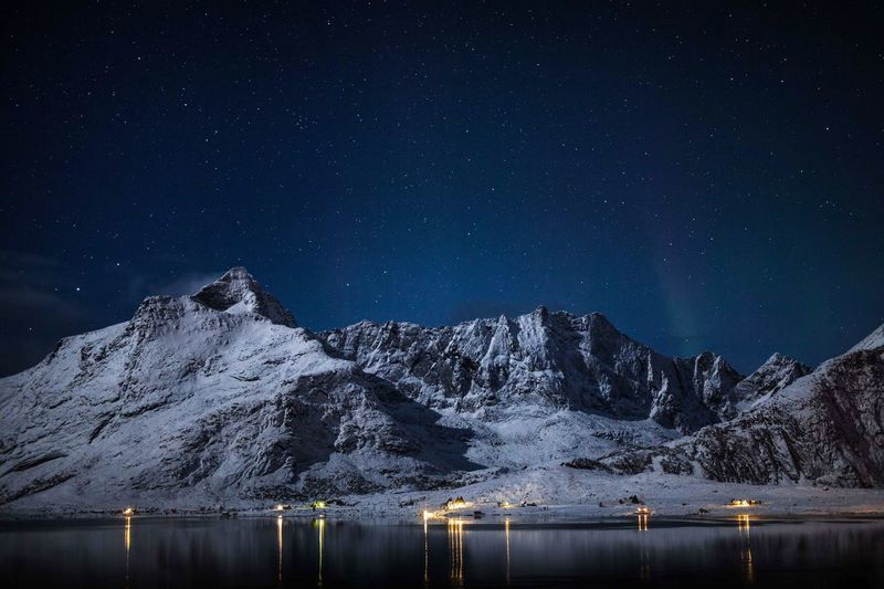 Scenic view of snowcapped mountains by lake against star field at night