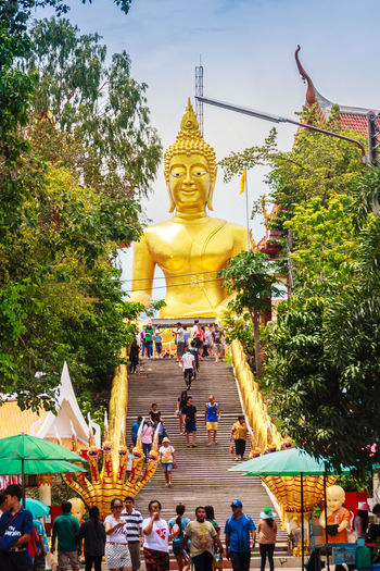 Pattaya, Thailand - May 2, 2015: Tourist and the Beautiful Entrance and steps leading up to the giant Buddha temple in Pattaya, Thailand Big Buddha Golden Buddha Image Stairs Stairway Architecture Buddha Statue Buddhist Temple Day Giant Buddha Gold Colored Golden Buddha Golden Buddha Statue Golden Color Human Representation Large Group Of People Leisure Activity Male Likeness Men Outdoors Place Of Worship Real People Religion Sculpture Sky Spirituality Staircase Statue Tree