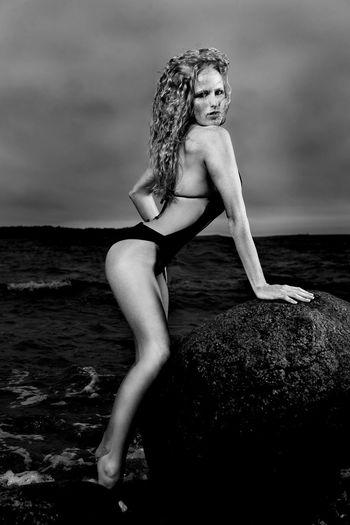 Young woman in bikini on rock at sea shore
