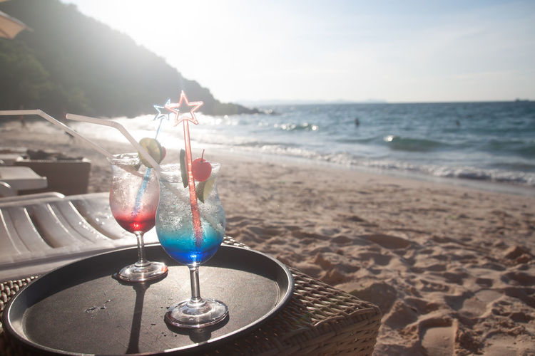Wine glass on table at beach against sky