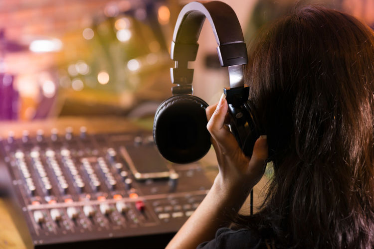Rear view of woman holding headphone while standing by audio equipment