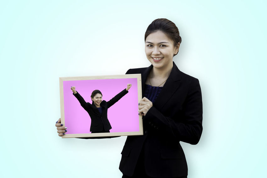 Asian business woman holding her self in white board Asian  Isolated Thai Win Woman Advertisement Billboard Blended Images Board Business Businesswoman Colored Background Concept Holding Looking At Camera People Portrait Showing Smiling Studio Shot Success Successful Suit Winner Young Women