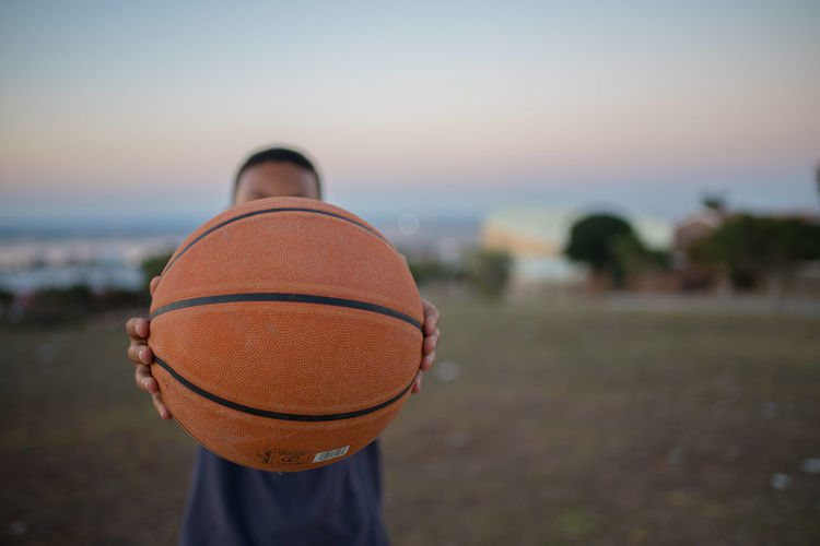 Close-up of man holding basketball while standing outdoors