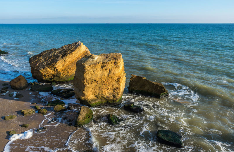 Scenic view of rocks on beach against sky