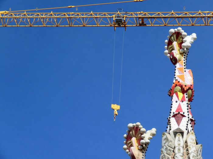 Low Angle View Of Crane At Sagrada Familia During Renovation Against Sky