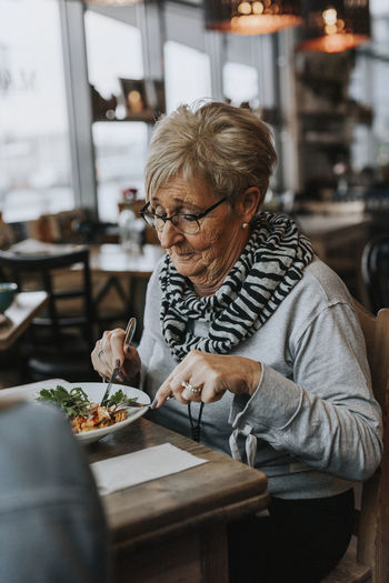 Woman sitting on table at restaurant