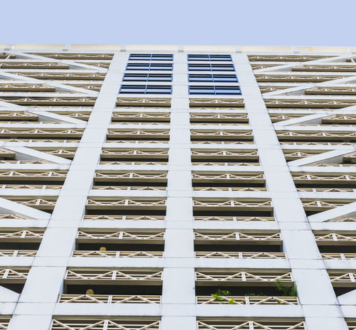 A lower view of tall building near the street in bangkok, pattern window, copy space. Construction High Industry Lines Low Angle View Modern Perspective Architecture Backgrounds Building Exterior Built Structure Close-up Concrete Day Design Downtown District Low Angle View No People Outdoors Pattern Sky Steel Street Structure Window