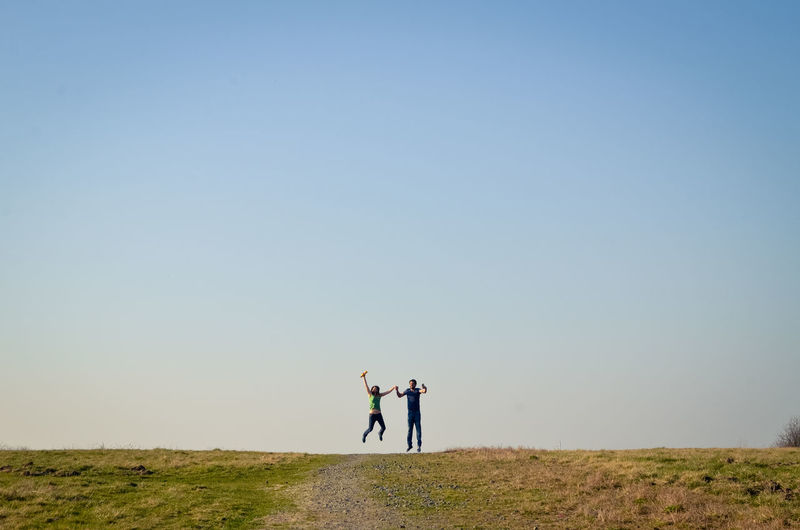 Couple jumping on land against clear sky
