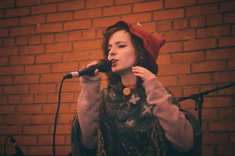Young woman singing against brick wall