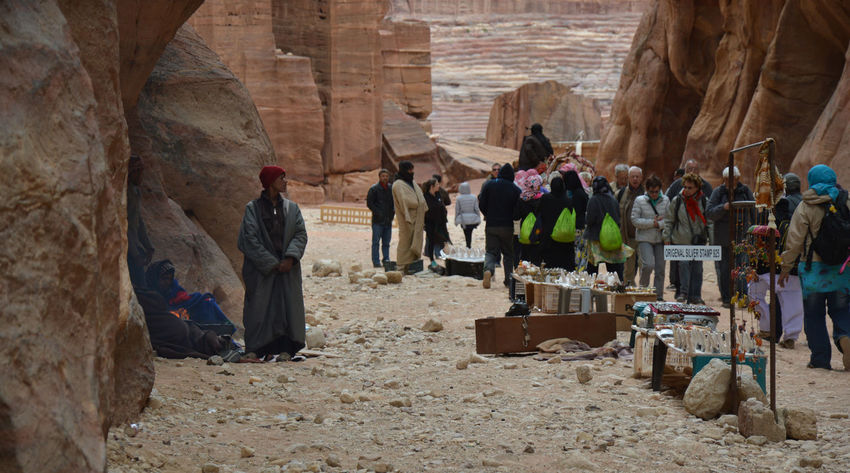 Beduin sellers of Petra rest in front of their stalls looking at the toutists who pass through. Petra is the famous archaeological site in Jordan's southwestern desert. Archaeological Sites Archeology Architecture Beduin Beduines Casual Clothing Day Desert Famous Place History Holiday Jordan Large Group Of People Petra, Jordan Rock Formation Sellers Shop Stalls The Past Tourism Tourist Tourist Attraction  Tourists Travel Vacations