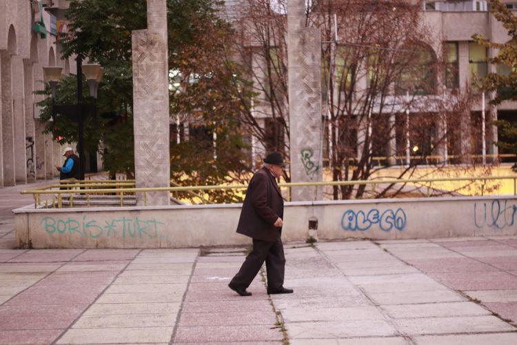 Full length of man walking on sidewalk in city