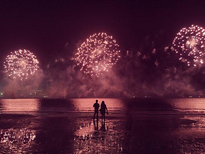 Silhouette Couple Enjoying Fireworks At Seashore