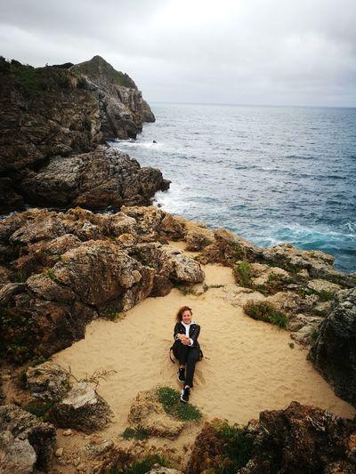 Full length of man on rocks at beach against sky